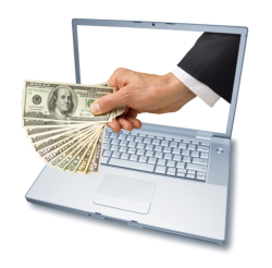 hand and money on a laptop